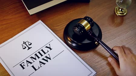 spravedlnost : Hand knocking gavel twice with family law document