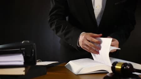 legal : A lawyer walks in, looks through a book, takes down some points  urgently and leaves