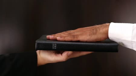 végrehajtó : Hand lifting bible up for taking an oath in court