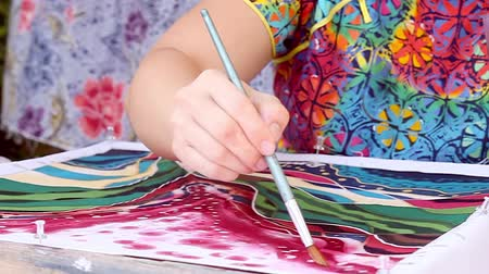 pan shot : Panning shot of crafwoman painting batik Stock Footage