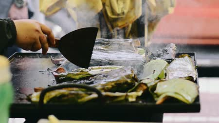 envolto : Grilling fish on a griddle at bazaar Ramadan Vídeos
