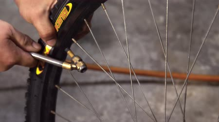 ремонтник : Closeup of pumping air to the bicycle tire