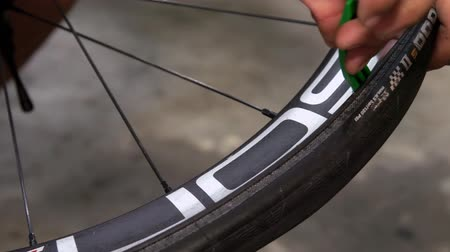 repairer : Closeup of taking off tire from the bicycle rim