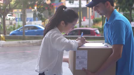 выражать : Young woman signing for her parcel