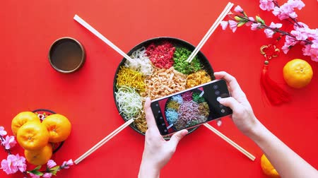 loção : Hands taking picture of the yee sang