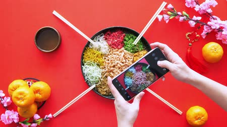 изобилие : Hands taking picture of the yee sang