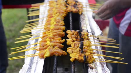 grelha : Street hawker grilling satay meat over a gas stove. Satay is a dish of seasoned, skewered and grilled meat, served with a sauce Vídeos