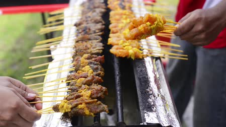 stragan : Street hawker grilling satay meat over a gas stove. Satay is a dish of seasoned, skewered and grilled meat, served with a sauce Wideo