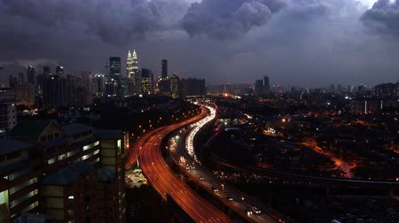 otoyol : A 4K video of Kuala Lumpur City Skyline at dusk with dramatic clouds with lightning. A motorway full of moving cars can be seen.
