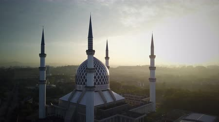 минарет : Aerial Shot - Sunrise at a mosque. Arabic writing on the done reads - Believe in one God. Drone flying forward slowly. Стоковые видеозаписи
