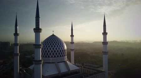 минарет : Aerial Shot - Sunrise at a mosque. Arabic writing on the dome reads - Believe in one God. Drone flying forward slowly. Стоковые видеозаписи