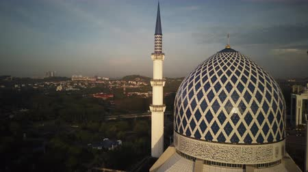 abdul : Aerial Shot - Sunrise at a mosque. Arabic writing on the dome reads - Believe in one God. Drone flying back slowly.