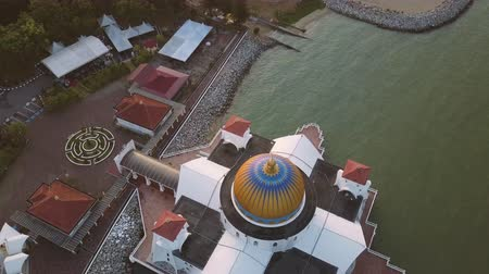 masjid selat melaka : Aerial Footage - Dawn at a mosque, The Melaka Straits Mosque, located on the man-made Malacca Island near Melaka City, Melaka, Malaysia. Color corrected with film look color LUT. Moody exposure. Drone moving back, camera tilt up,