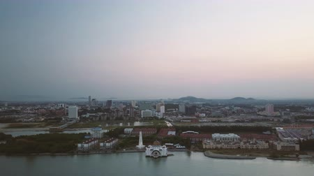 masjid selat melaka : Aerial Footage - Dawn at a mosque, The Melaka Straits Mosque, located on the man-made Malacca Island near Melaka City, Melaka, Malaysia. Color corrected with film look color LUT. Moody exposure. Drone wide shot. Stock Footage