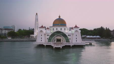 masjid selat melaka : Aerial Footage - Dawn at a mosque, The Melaka Straits Mosque, located on the man-made Malacca Island near Melaka City, Melaka, Malaysia. Color corrected with film look color LUT. Moody exposure. Drone moving back