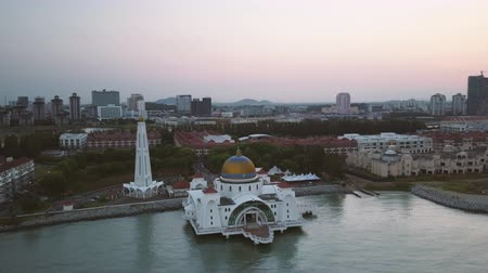 masjid selat melaka : Aerial Footage - Dawn at a mosque, The Melaka Straits Mosque, located on the man-made Malacca Island near Melaka City, Melaka, Malaysia. Color corrected with film look color LUT. Moody exposure. Drone dolly Stock Footage