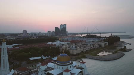 masjid selat melaka : Aerial Footage - Dawn at a mosque, The Melaka Straits Mosque, located on the man-made Malacca Island near Melaka City, Melaka, Malaysia. Color corrected with film look color LUT. Moody exposure. Drone moving forward. Stock Footage