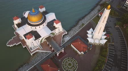 masjid selat melaka : Aerial Footage - Dawn at a mosque, The Melaka Straits Mosque, located on the man-made Malacca Island near Melaka City, Melaka, Malaysia. Color corrected with film look color LUT. Moody exposure. Top Down Shot