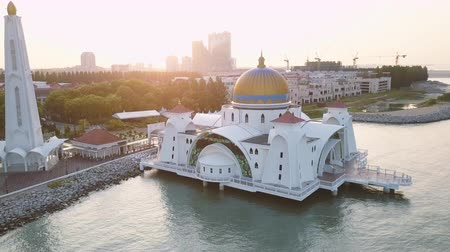 masjid selat melaka : Aerial Footage - Dawn at a mosque, The Melaka Straits Mosque, located on the man-made Malacca Island near Melaka City, Melaka, Malaysia. Color corrected with film look color LUT. Moody exposure. Drone pan right Stock Footage