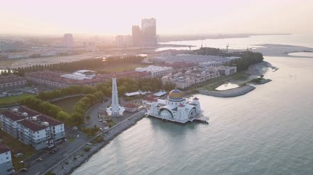 masjid selat melaka : Aerial Footage - Dawn at a mosque, The Melaka Straits Mosque, located on the man-made Malacca Island near Melaka City, Melaka, Malaysia. Color corrected with film look color LUT. Moody exposure. Drone moving forward camera tilt