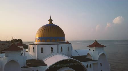 masjid selat melaka : Aerial Footage - Dawn at a mosque, The Melaka Straits Mosque, located on the man-made Malacca Island near Melaka City, Melaka, Malaysia. Color corrected with film look color LUT. Moody exposure. Drone moving forward