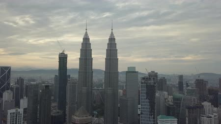 outside view : Aerial Footage of Kuala Lumpur at Sunrise with Petronas Towers, the tallest twin towers visible. Drone tracking shot. Flat Color Profile, low contrast, low saturation.