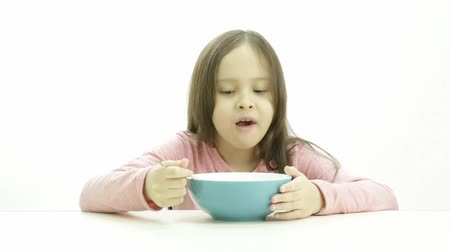 cereais : A cute young girl in a pink top eating her morning bowl of cereal