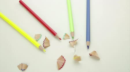 papeteria : Pencil shavings falling on colorful pencil crayons on a desktop Wideo