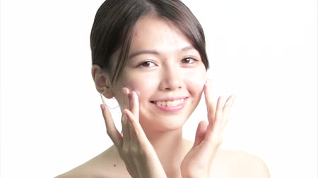 уход за кожей : Chinese Woman Applying Cream to Face with Hands, Medium Close Up in studio on white background
