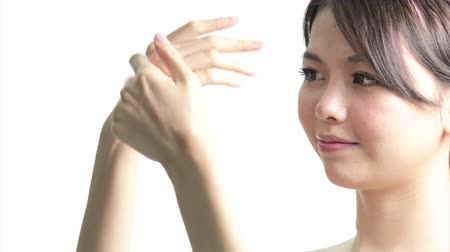 pleťová voda : Chinese Woman Applying Cream to Hands, Medium Close Up in studio on white background