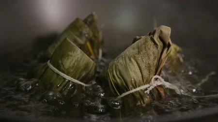dimsum : Zongzi boiling in a wok. Zongzi is a traditional Chinese food eaten during dragon boat festival.