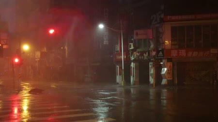 ulewa : Heavy rain on street corner during typhoon blowing debri slow motion1 -