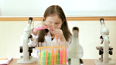 experiment : Young scientist sitting in lab mixing liquids in test tubes in science lab