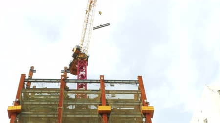 Tower crane moving I-beam, logos and faces blurrred Стоковые видеозаписи