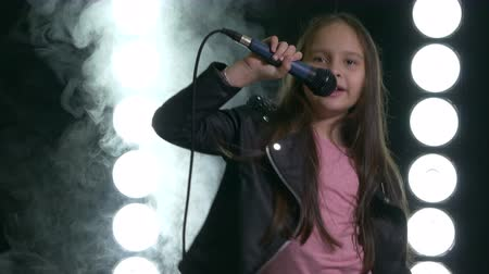 Young Asian American girl singing and bowing with smoke and stagelight in background.