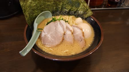 ramen : A delicious looking bowl of tonkotsu ramen with extra pork chashu and egg Stock Footage