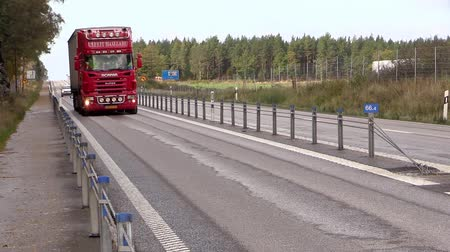 ciężarówka : Red truck passing by on straight road. Protective cable barriers part traffic and add safety. Wildlife fencing keeps animals from beeing hit.