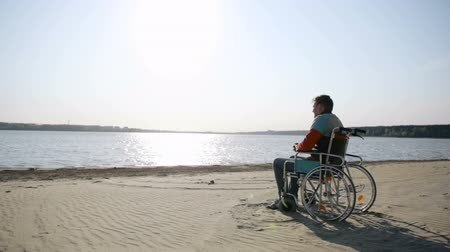 idősek : Man sitting in a wheelchair on the sea shore