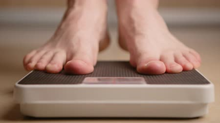 com escamas : man standing on weight scale Stock Footage