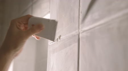 устанавливать : Worker putting tiles on the wall in the kitchen. His hands are placing the tile on the adhesive.