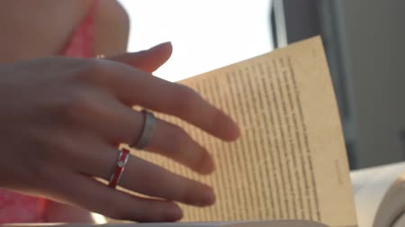 castilian : Womans hand beautifully turns over the pages of the paper book in Bright Sun at Sunset