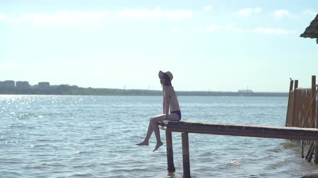 platform edge : Woman relaxes sitting on the edge of a wooden jetty, legs swing near the water surface in the background.