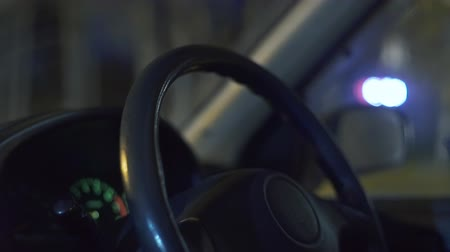 tachometer : woman driving her modern car at night in a city.
