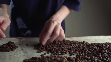 close up woman hands sorting poor qualitys of rusted coffee beans. Stok Video