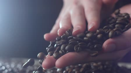 restaurante : Aromatic roasted coffee beans being held over a table, hands testing quality in slow motion