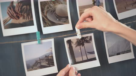 Woman hanging photo of her travel on the wall, vacation photos.