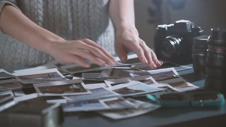 Woman with instant print transfer pictures in hands. looking at photos of road trip in dark room. table with photos, lens, photo camera.