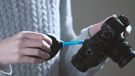 Photographer cleaning camera lens with a blower. Stock Footage