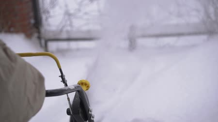 A man cleans snow from sidewalks with snowblower. Stok Video