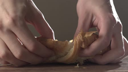 Close-up of a girls hands breaks a fresh croissant, slow motion. Fresh sweet pastries, close-up Stok Video
